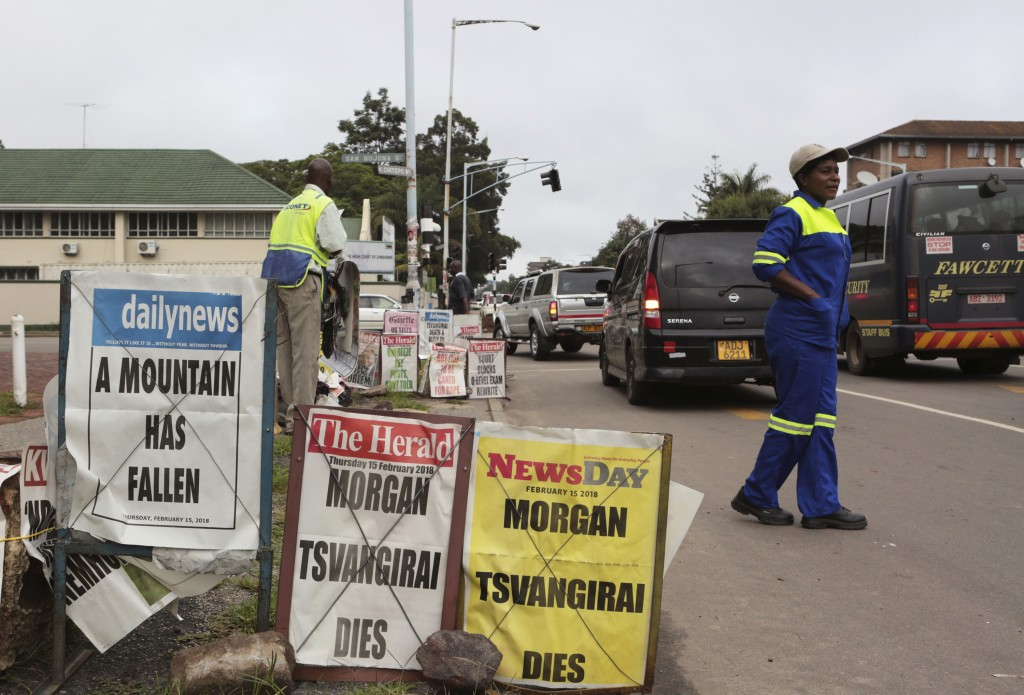 A woman crosses the road near newspaper headlines in Harare, Zimbabwe Thursday, Feb, 15, 2018. Zimbabwean opposition leader Morgan Tsvangirai died Wed