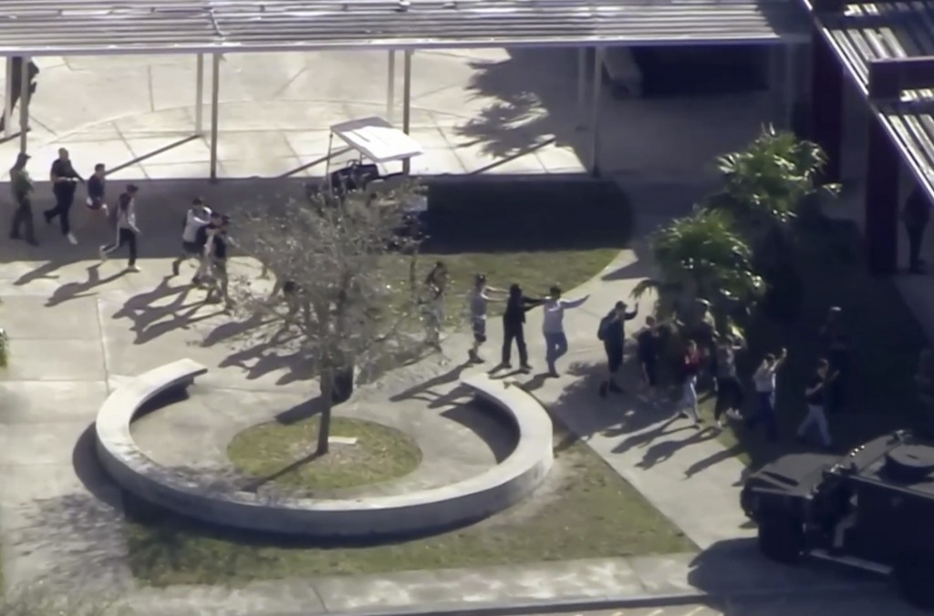 In this frame grab from video provided by WPLG-TV, students from the Marjory Stoneman Douglas High School in Parkland, Fla., evacuate the school follo