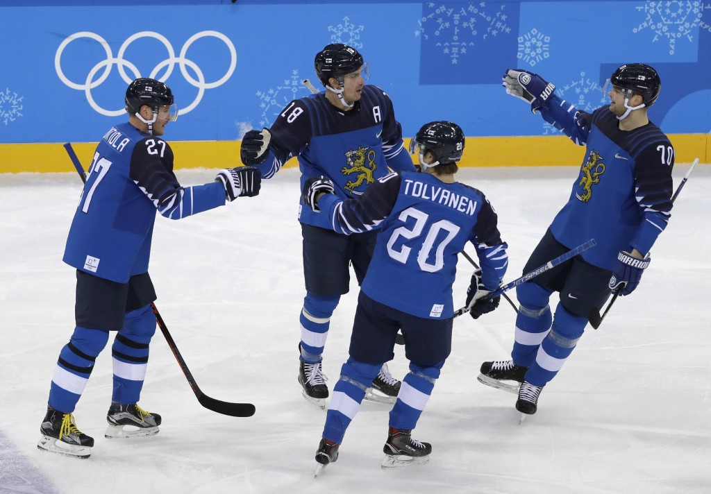 Sami Lepisto (18), of Finland, celebrates with his teammates after scoring a goal against Germany during the first period of the preliminary round of