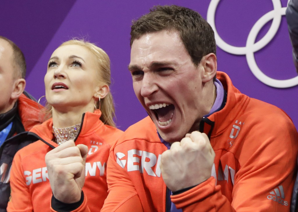 Aljona Savchenko and Bruno Massot of Germany react as their scores are posted following their performance in the pairs free skate figure skating final