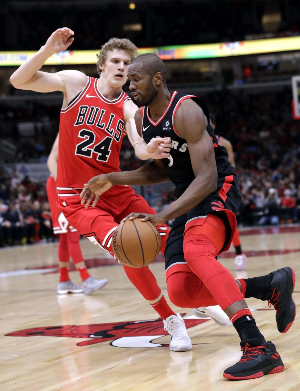 Toronto Raptors forward/center Serge Ibaka, right, drives against Chicago Bulls forward Lauri Markkanen during the first half of an NBA basketball gam