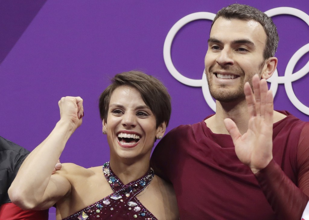 Meagan Duhamel and Eric Radford of Canada react as their scores are posted following their performance in the pairs free skate figure skating final in