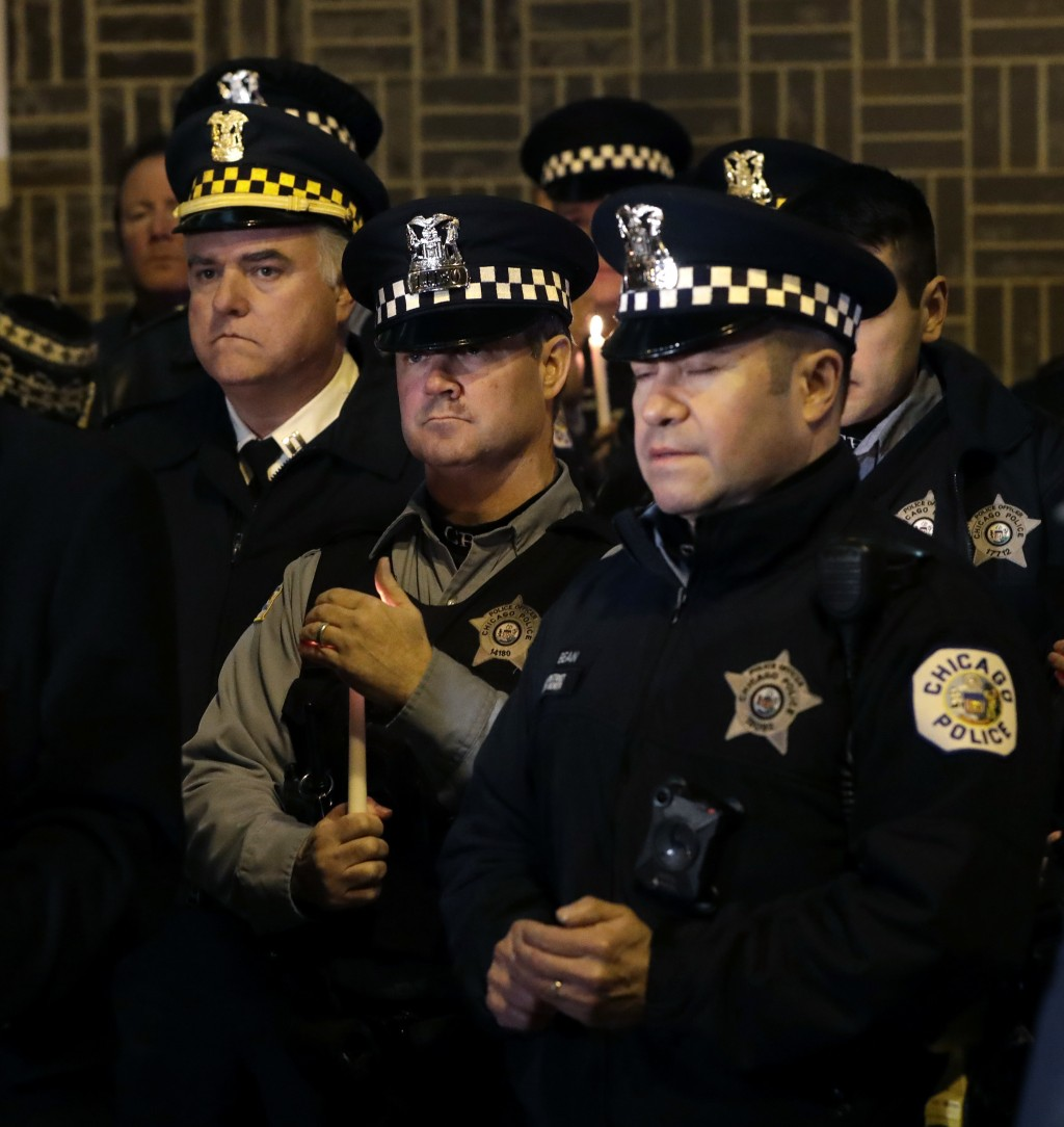 Chicago police officers gather for a candlelight vigil for police Cmdr. Paul Bauer outside the Near North District headquarters Wednesday, Feb. 14, 20
