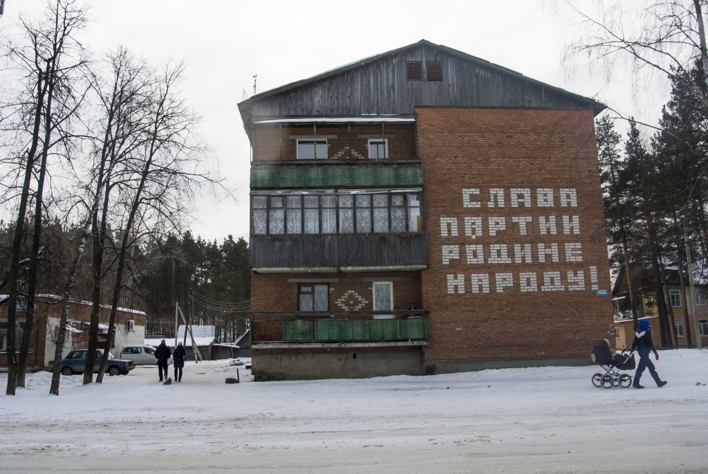 """People walk past a house with a Soviet-era slogan that reads """"Glory to the Party, Motherland and People!"""" in the village of Kedrovoye, Russia, Thursda"""