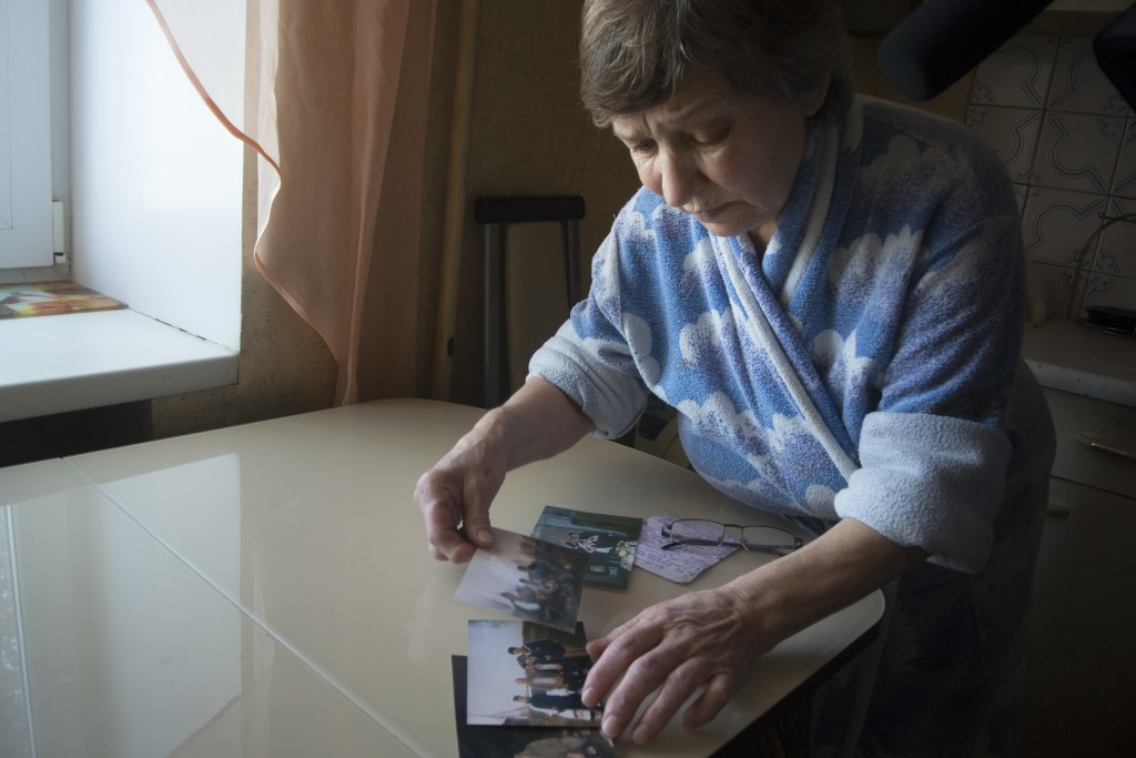 Farkhanur Gavrilova looks at the photos of her son Ruslan Gavrilov in the village of Kedrovoye, Russia, Thursday, Feb. 15, 2018. Gavrilova's son Rusla
