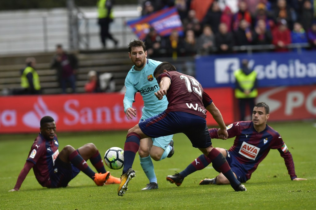 FC Barcelona's Lionel Messi competes for the ball with players from SD Eibar's Cote during the Spanish La Liga soccer match between FC Barcelona and S...