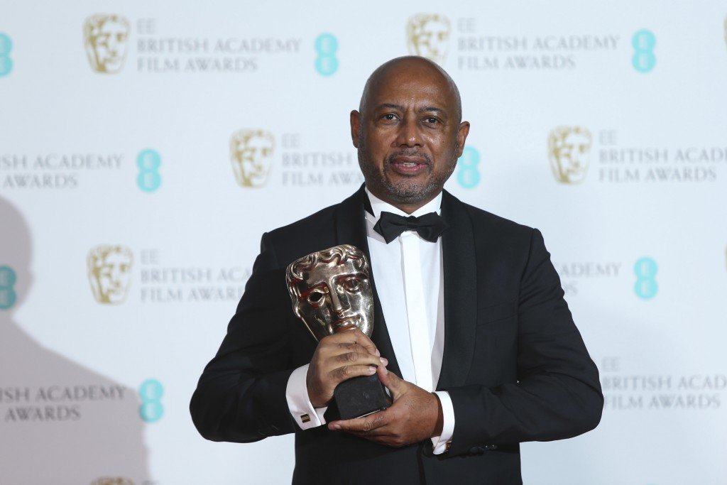 Filmmaker Raoul Peck holds his award for Best Documentary for 'I Am Not Your Negro' backstage at the BAFTA 2018 Awards in London, Sunday, Feb. 18, 201...