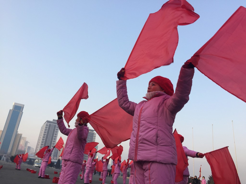 In this Feb. 2, 2018 photo, women wave flags and dance during the early morning rush hour in Pyongyang, North Korea. The performances, which are inten...