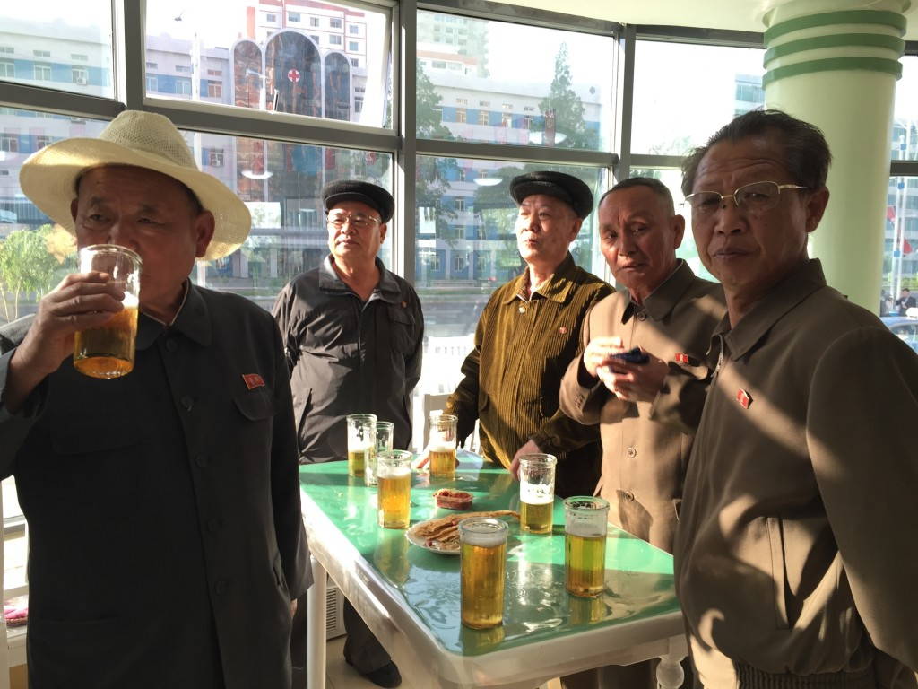 In this May 7, 2016 photo, men, wearing loyalty pins bearing portraits of former leaders Kim Il Sung or Kim Jong Il, or both, take a break in a beer h...