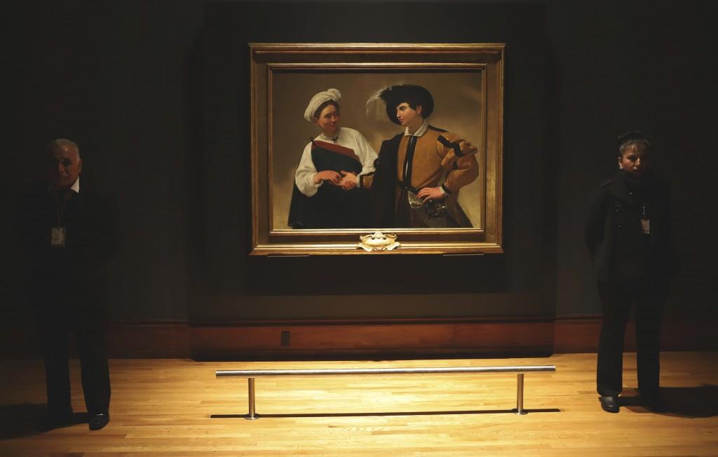 Museum workers stand next to 'La Buona Ventura' by Italian master Michelangelo Merisi da Caravaggio (1571-1610) during the opening of a Caravaggio exh