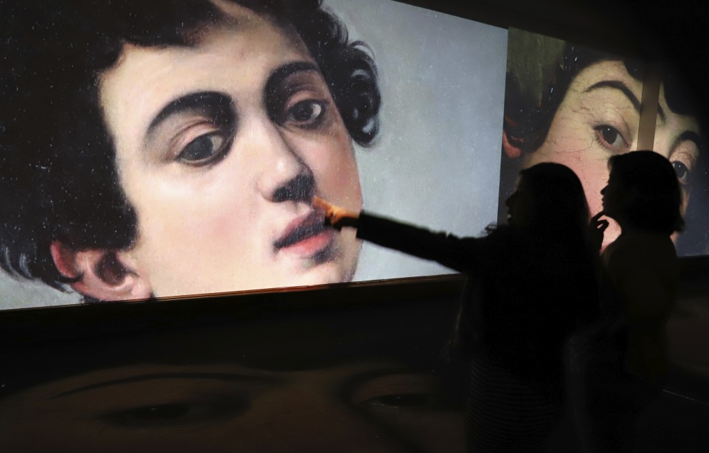 Visitors look at a projection of a painting by Italian master Michelangelo Merisi da Caravaggio (1571-1610) during the opening of a Caravaggio exhibit