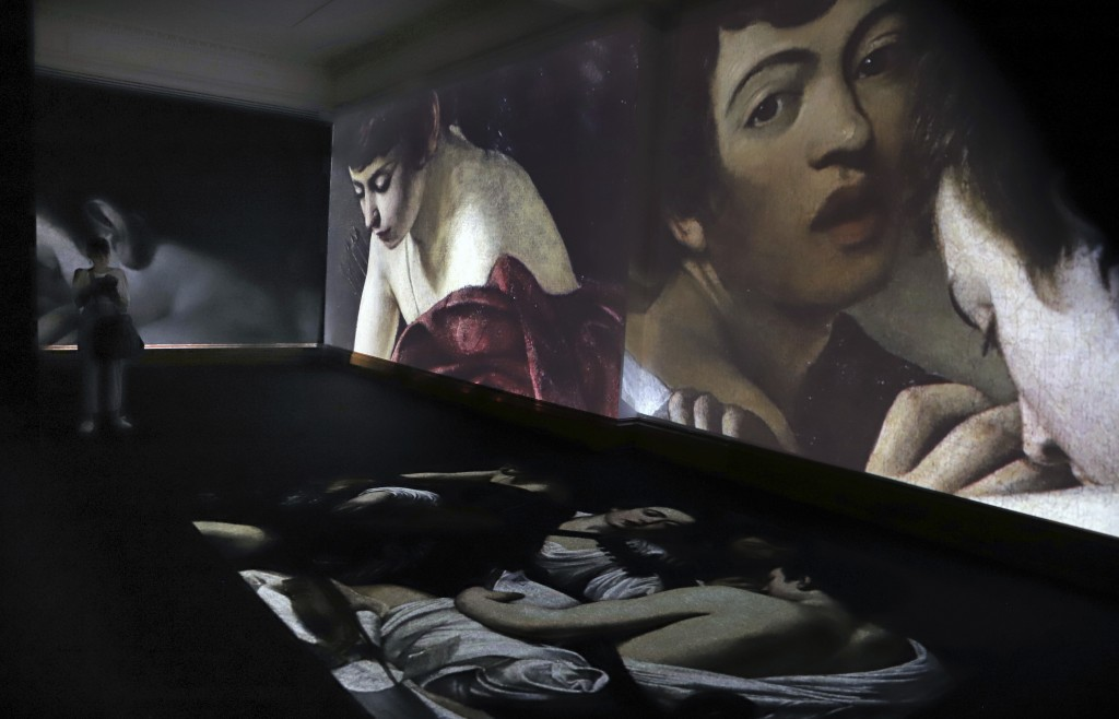 Visitors look at a multimedia projection of the work of Italian master Michelangelo Merisi da Caravaggio (1571-1610) during the opening of a Caravaggi