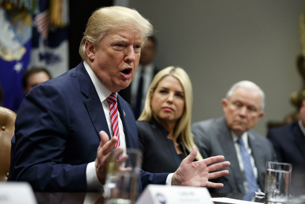 Florida Attorney General Pam Bondi, center, and Attorney General Jeff Sessions, right, watch as President Donald Trump speaks during a meeting with st...