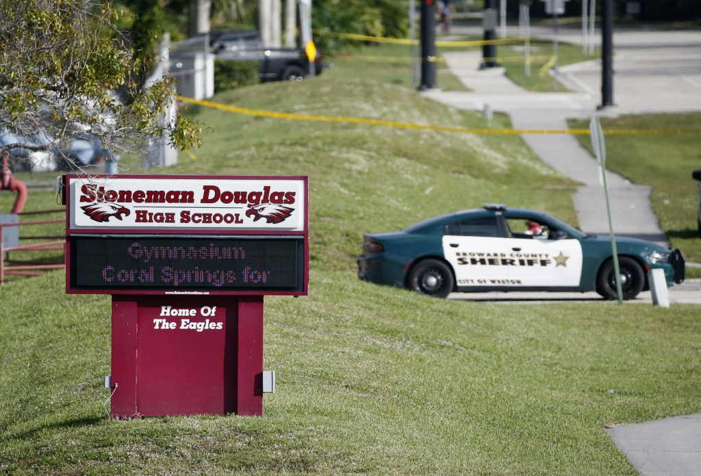 FILE- In this Feb. 15, 2018, file photo, Law enforcement officers block off the entrance to Marjory Stoneman Douglas High School, in Parkland, Fla., a