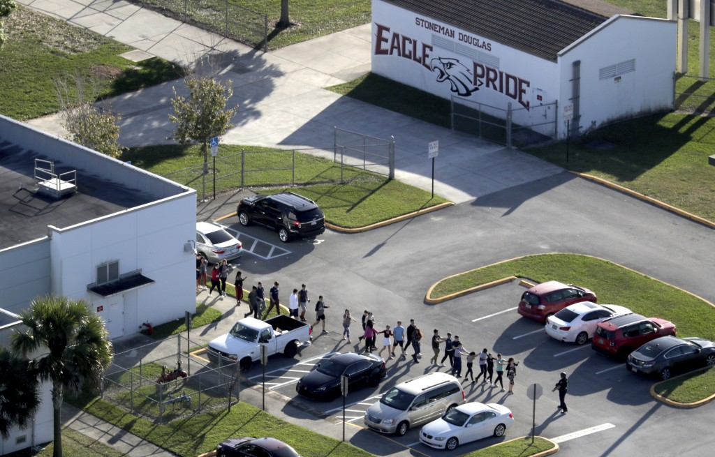 FILE- In this Feb. 14, 2018, file photo, students are evacuated by police from Marjory Stoneman Douglas High School in Parkland, Fla., after a shooter