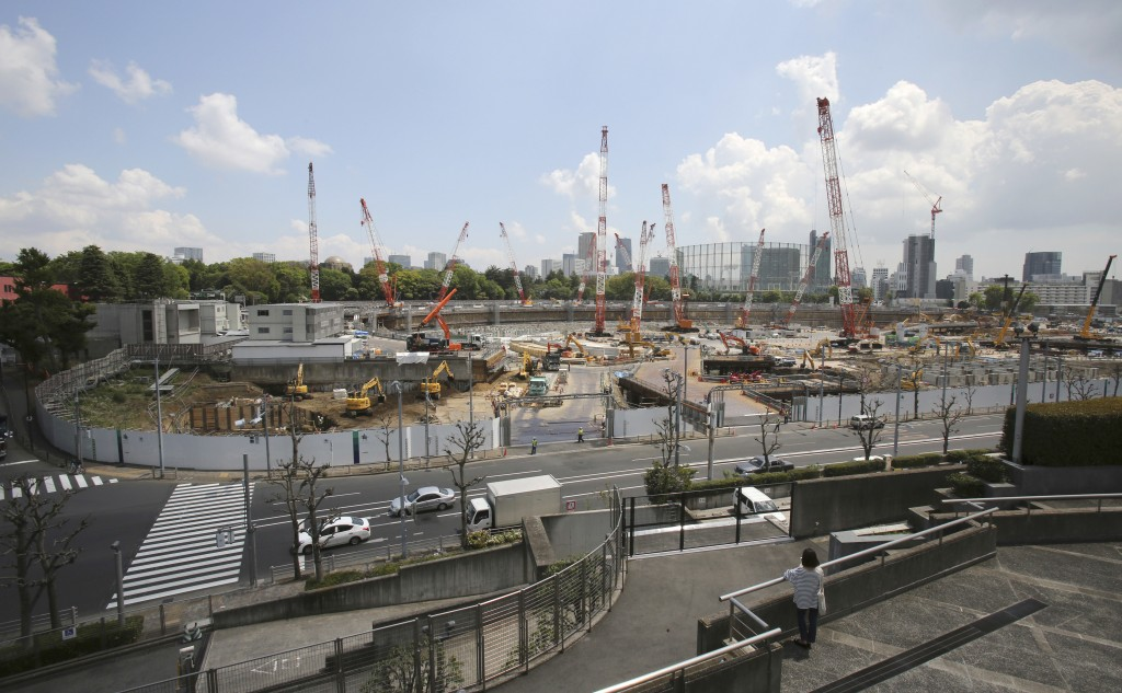 FILE - In this April 28, 2017, file photo, a woman looks at the construction site of the new National Stadium for the 2020 Tokyo Olympics and Paralymp...