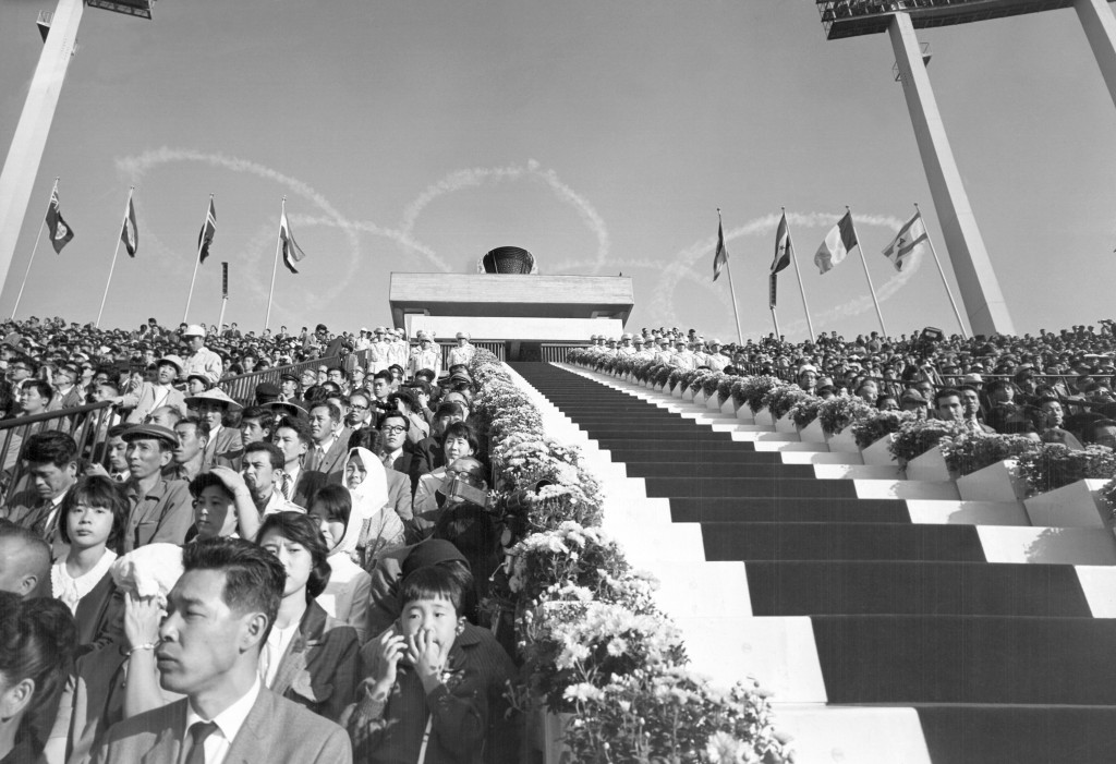 FILE - In this Oct. 10, 1964, file photo, five interlocking Olympic rings are thrown high in the sky by jet planes drift over the stadium during the o...