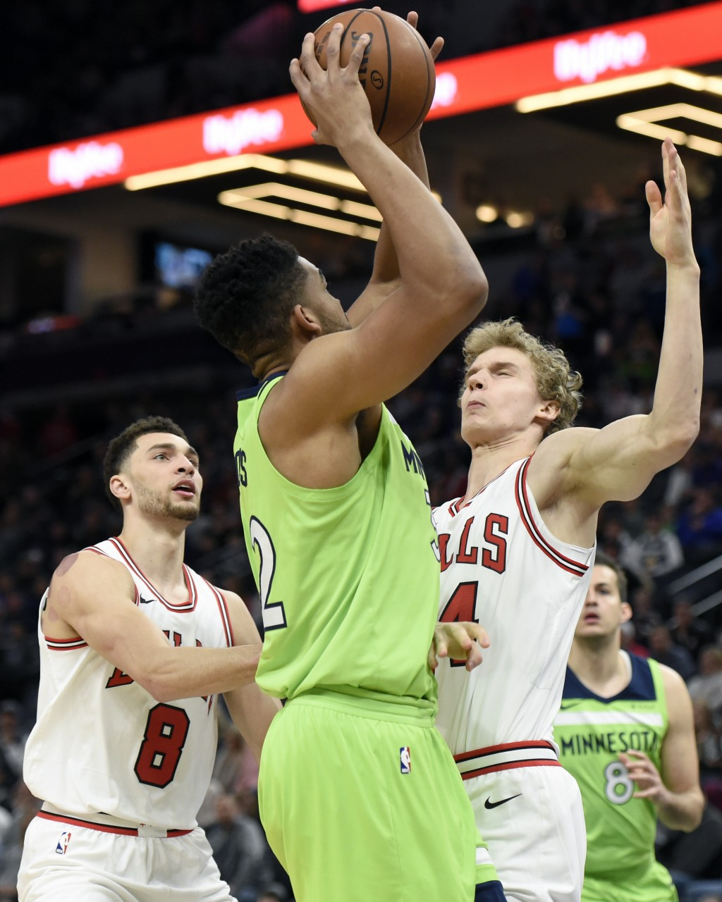 Minnesota Timberwolves' Karl-Anthony Towns, center, shoots against Chicago Bulls' Zach LaVine (8) and Lauri Markkanen, of Finland, during the first qu...