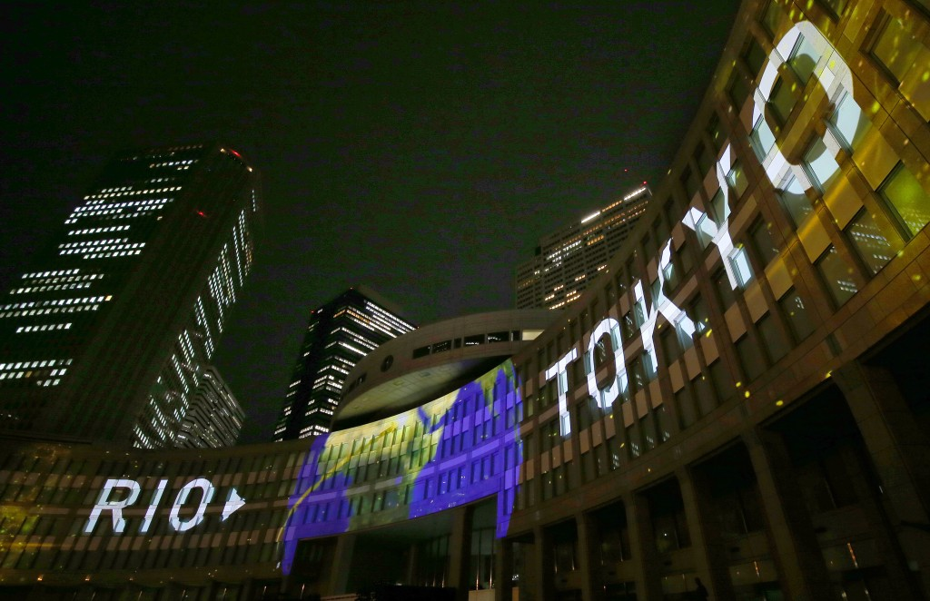 FILE - In this July 24, 2017, file photo, images are illuminated on the Tokyo Metropolitan Government building during the Tokyo 2020 flag tour festiva...
