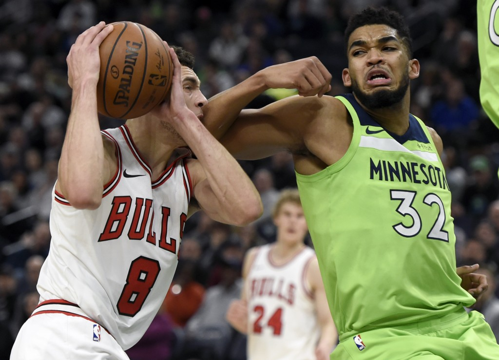 Minnesota Timberwolves' Karl-Anthony Towns (32) fouls Chicago Bulls' Zach LaVine (8) during the third quarter of an NBA basketball game on Saturday, F...