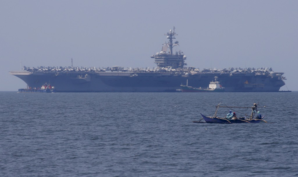 FILE - In this Feb. 17, 2018, file photo, fishermen on board a small boat pass by the USS Carl Vinson aircraft carrier at anchor off Manila, Philippin...