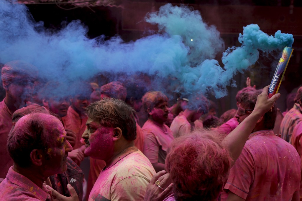 In this Feb. 28, 2018 photo, locals light up a color smoke candle as a procession of Hindu's lord Krishna's chariot moves through a street during Holi...