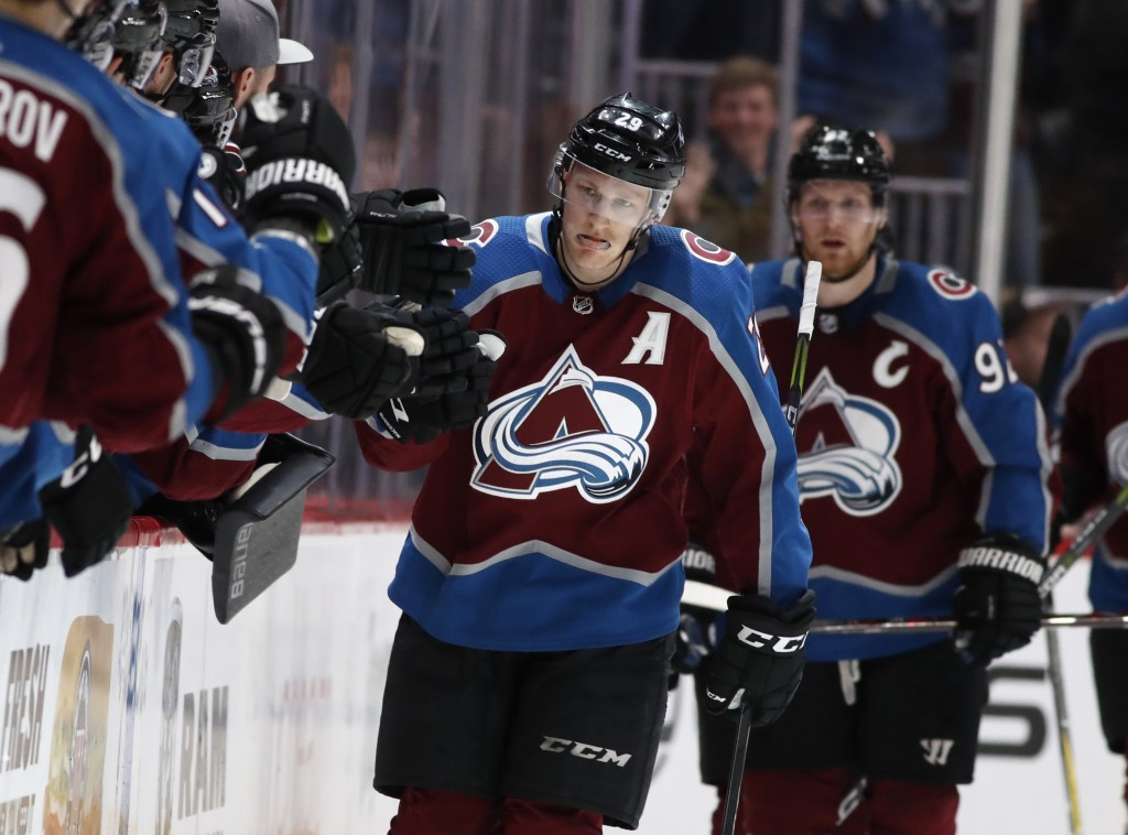 Colorado Avalanche center Nathan MacKinnon, center, is congratulated as he passes the team box after scoring a goal against the Calgary Flames during