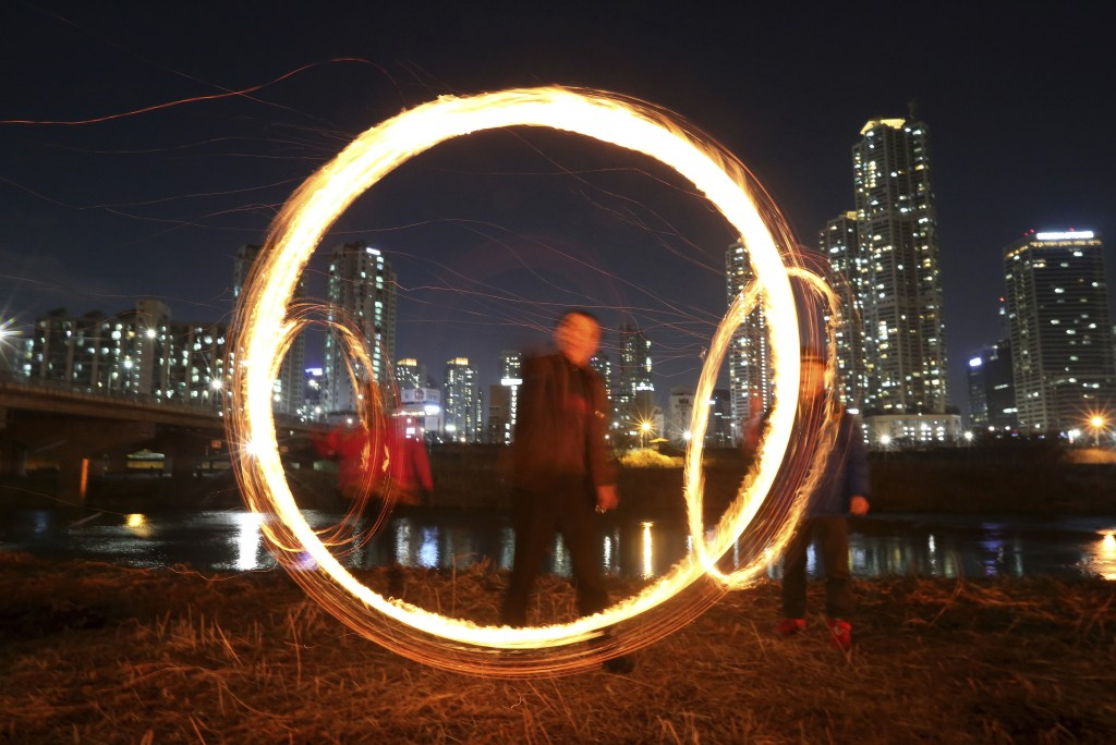 In this March 1, 2018 photo, people twirl cans filled with burning wood chips and straw to celebrate the first full moon of the Lunar New Year in Seou...