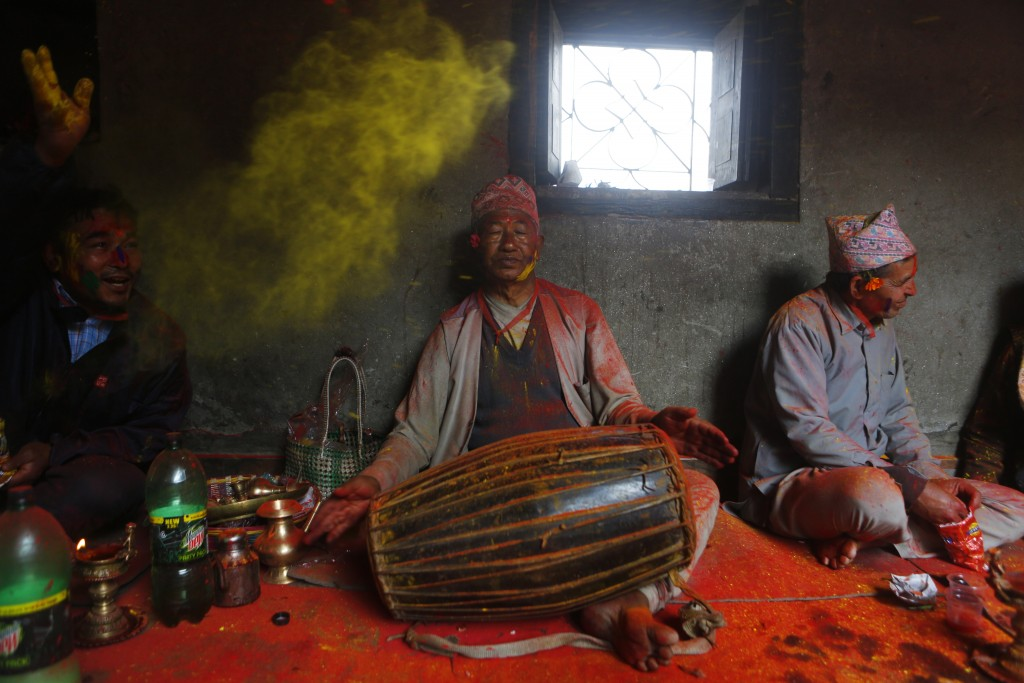 A local man throws color as another plays a traditional drum during Holi celebrations in Bhaktapur, Nepal, Thursday, March 1, 2018. The festival marks...