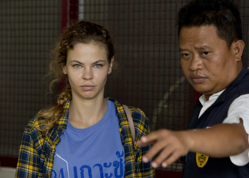 In this Feb. 28, 2018 photo, a police officer escorts Anastasia Vashukevich from a detention center in Pattaya, south of Bangkok, Thailand, after she ...