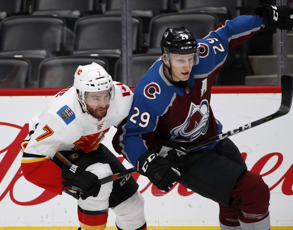 Calgary Flames defenseman TJ Brodie, left, uses his stick to slow Colorado Avalanche center Nathan MacKinnon during the third period of an NHL hockey