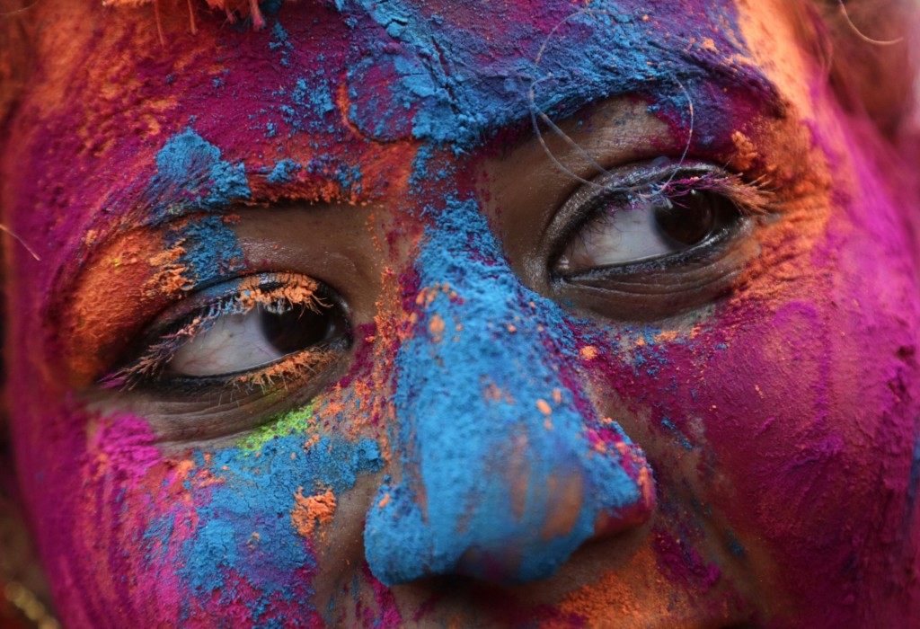 The face of a woman is smeared with colored powder during Holi, the Hindu festival of colors in Kolkata, India, Thursday, March 1, 2018. (AP Photo/Bik...