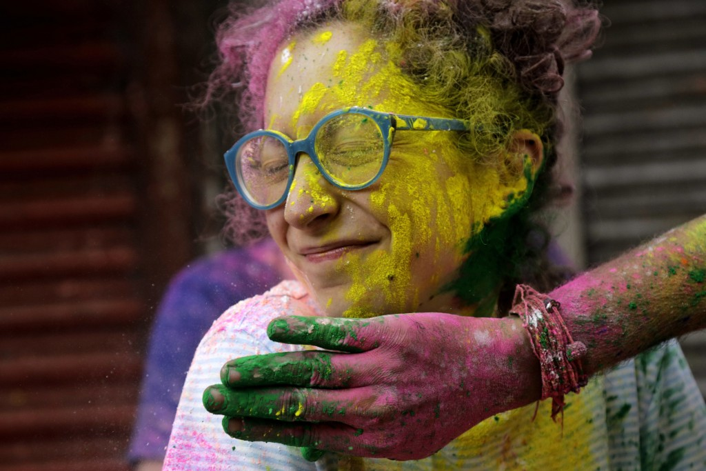 A tourist squints as local man puts colored powder on her face during the celebration of Holi in Kolkata, India, Thursday, March 1, 2018.  (AP Photo/B...