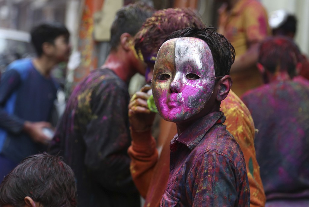 Locals play with masks and colored powder during Holi festival celebrations in Jammu, India, Thursday, March 1, 2018. (AP Photo/Channi Anand)