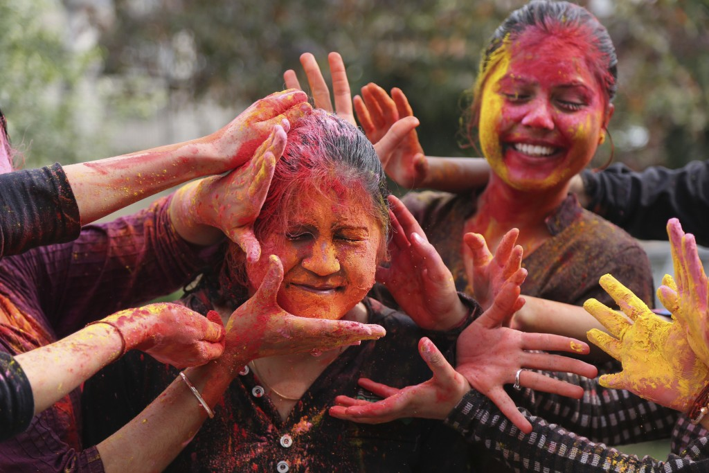 In this March 1, 2018 photo, Indian girls smear colored powder on each other as they celebrate Holi in Jammu, India. Holi, which is also called festiv...