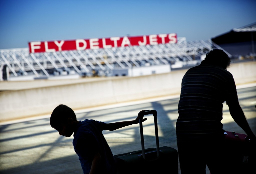 FILE- In this Oct. 13, 2016, file photo, passengers unload in front of a Delta Air Lines sign at Hartsfield-Jackson Atlanta International Airport, in