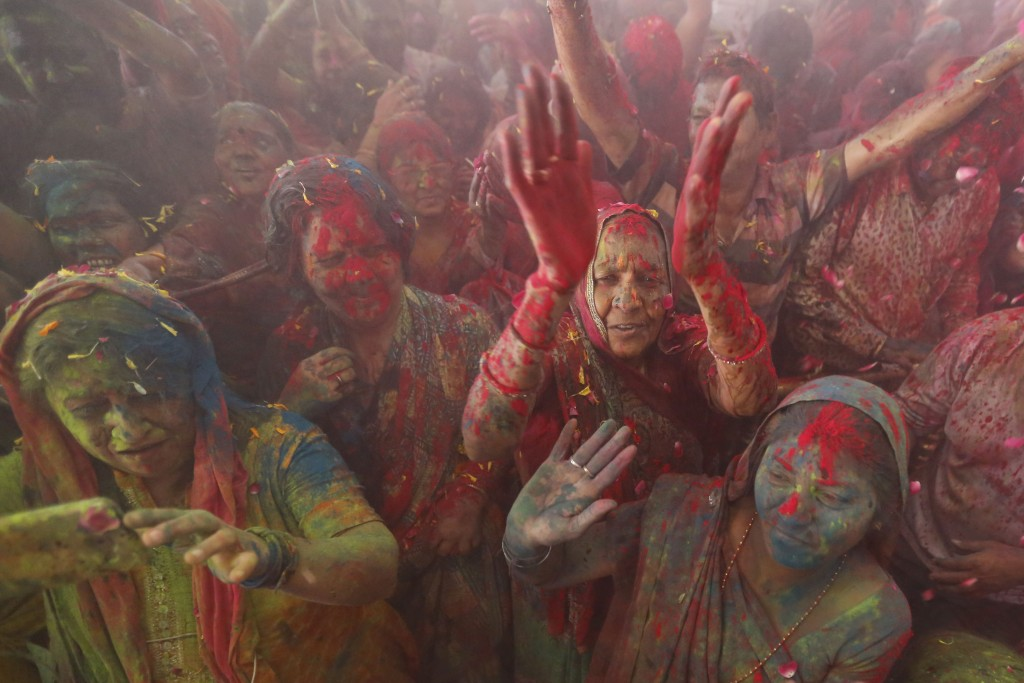 Hindu devotees dance amid colored powder and flowers thrown on them during Holi festival celebration at the Lord Jagannath temple in Ahmadabad, India,...