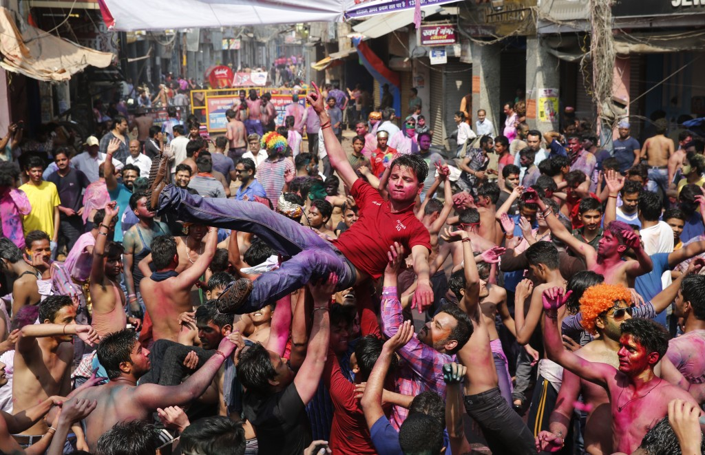 Indian revelers, faces smeared with colored powder, dance during celebrations to mark Holi, the Hindu festival of colors in Allahabad, India, Friday, ...