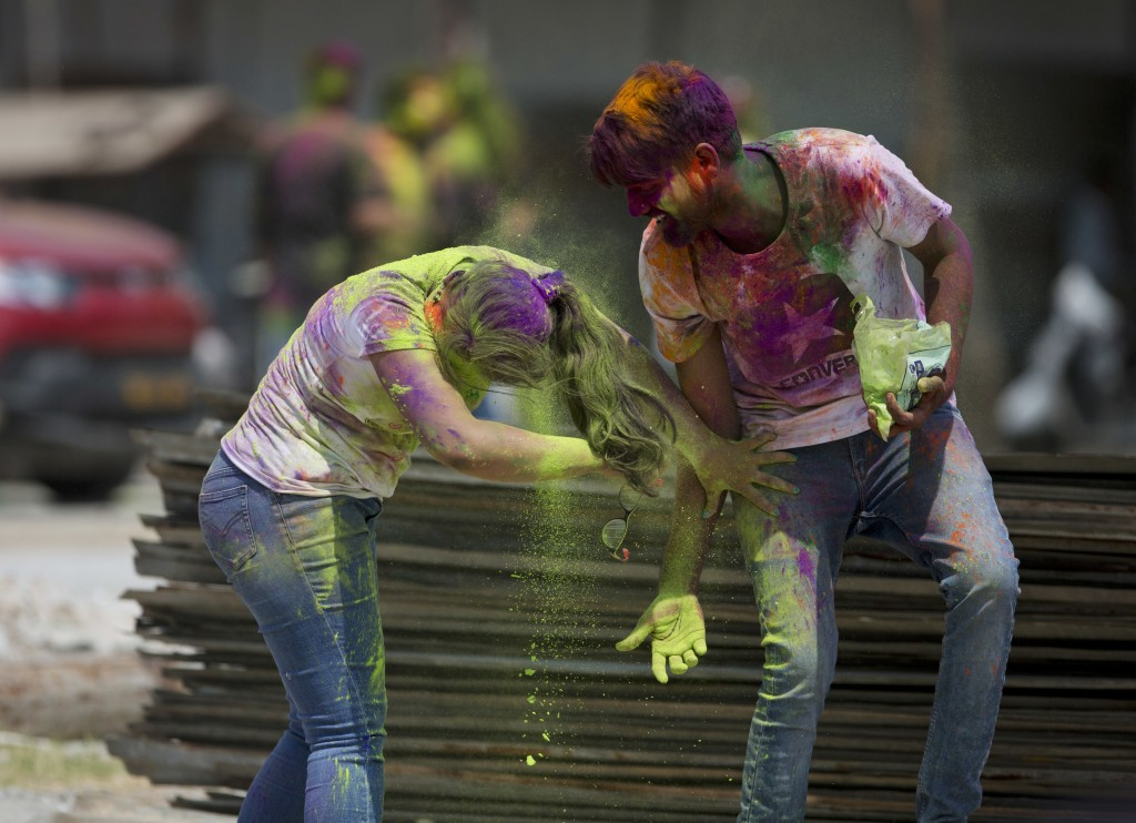 Locals throw colored powder on each other during Holi festival celebrations in Hyderabad, India, Friday, March 2, 2018. (AP Photo /Mahesh Kumar A.)