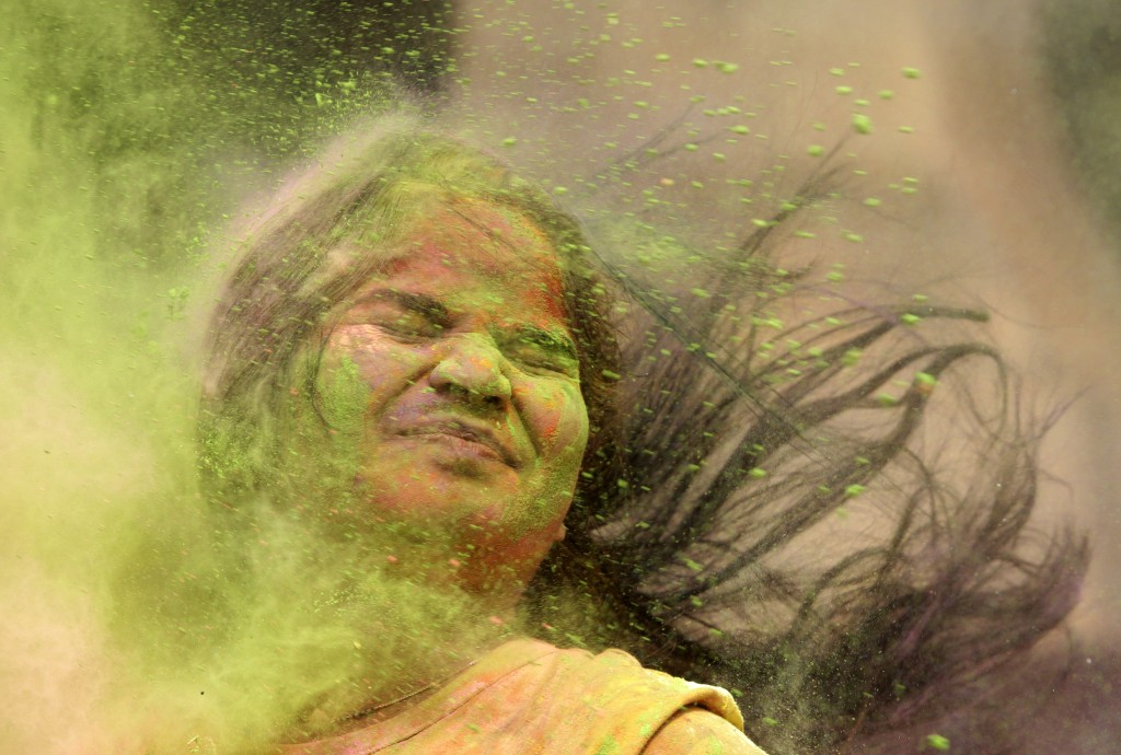 A girl reacts as colored powder is thrown at her during celebration of Holi in Mumbai, India, Friday, March. 2, 2018. (AP Photo/Rajanish Kakade)