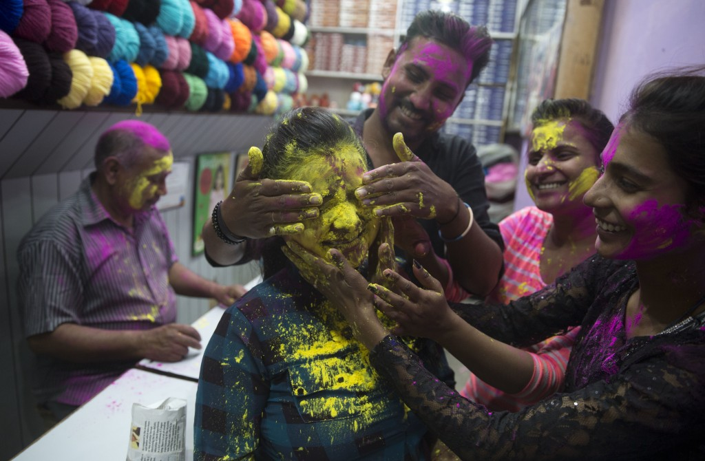 "In this Thursday, March 1, 2018, file photo, Locals smear colors on a girl's face as they celebrate ""Holi,"" in Allahabad, India. (AP Photo/Rajesh Kuma..."