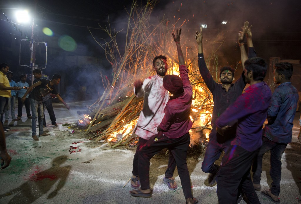 In this Thursday, March 1, 2018, file photo, locals dance around a bonfire during Holi festival celebrations in Allahabad, India. (AP Photo/Rajesh Kum...
