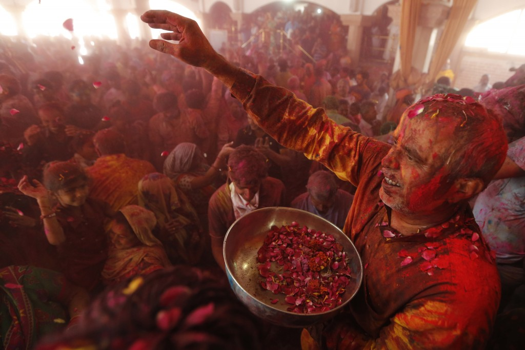 A man throws flowers out to devotees during Holi festival celebration at the Lord Jagannath temple in Ahmadabad, India, Friday, March 2, 2018. (AP Pho...
