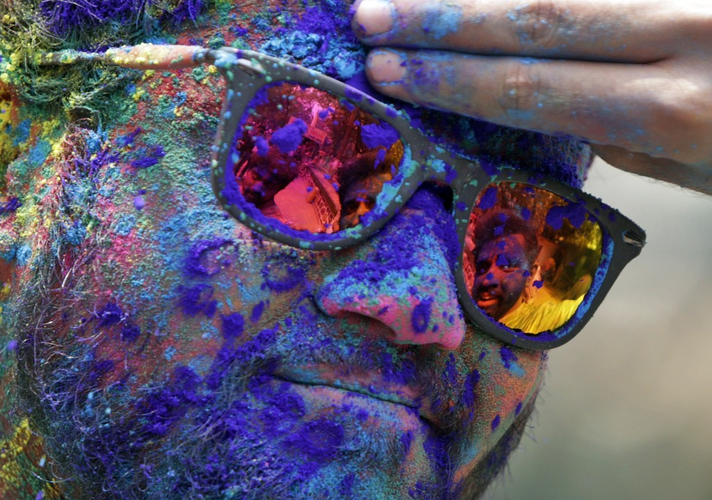 A man's face is smeared with color by another during festivities for Holi, the Hindu festival of colors, in Mumbai, India, Friday, March. 2, 2018. (AP...