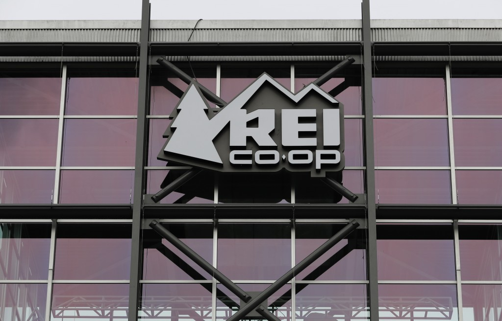 A sign at the REI flagship store is shown Friday, March 2, 2018, in Seattle. The outdoor retailer says it's halting future orders of some popular bran