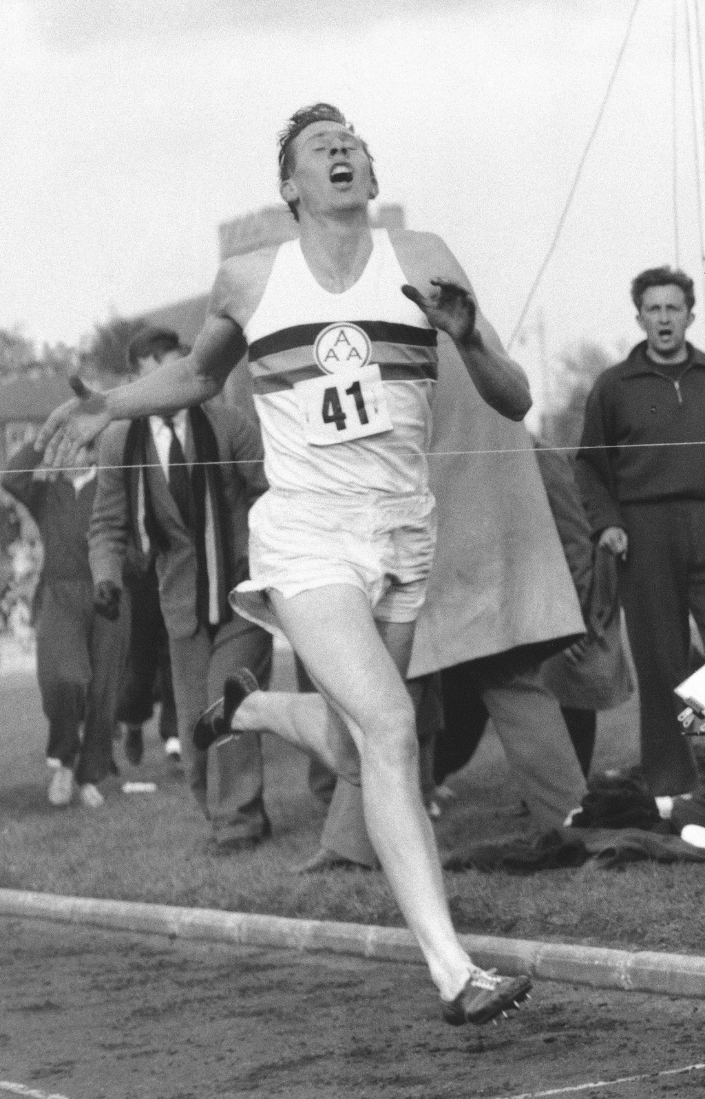 FILE - In this May 6, 1954 file photo, Britain's Roger Bannister hits the tape to break the four-minute mile in Oxford, England. A statement released ...