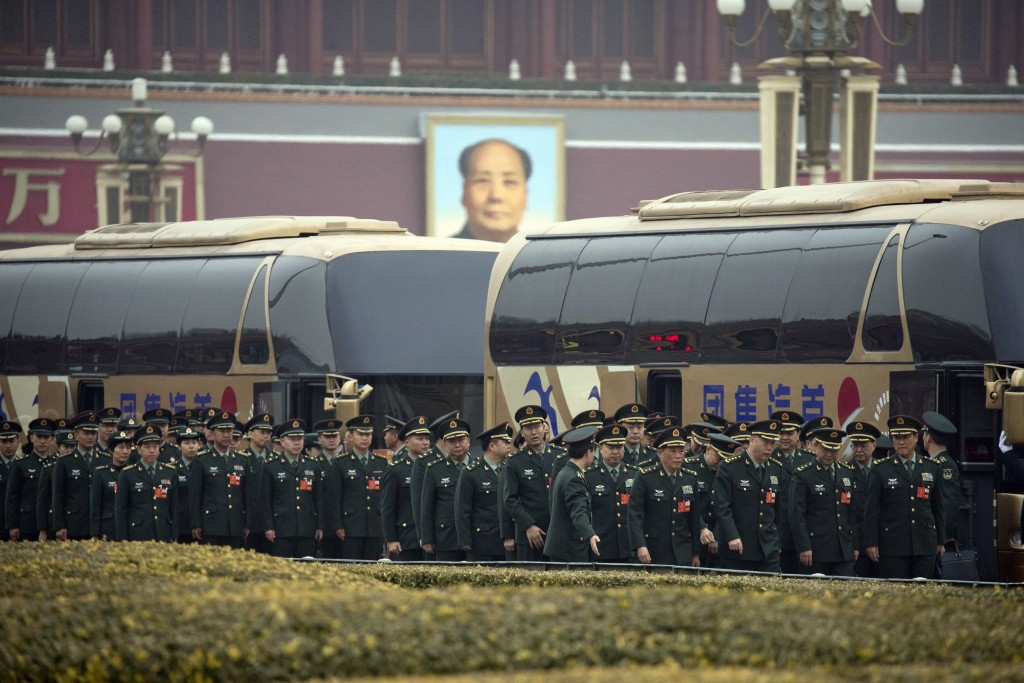 Military delegates arrive on buses near Tiananmen Gate with a giant portrait of Mao Zedong outside the Great Hall of the People on the eve of the annu