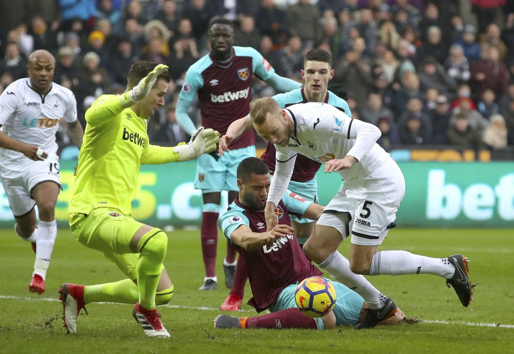 West Ham United's Winston Reid, centre, and Swansea City's Mike van der Hoorn, right, in action during their English Premier League soccer match at th...