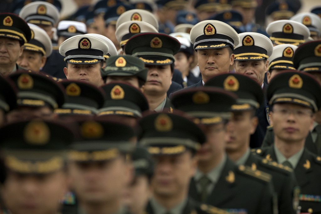 Military delegates arrive for a meeting at the Great Hall of the People ahead of Monday's opening session of China's National People's Congress (NPC) ...