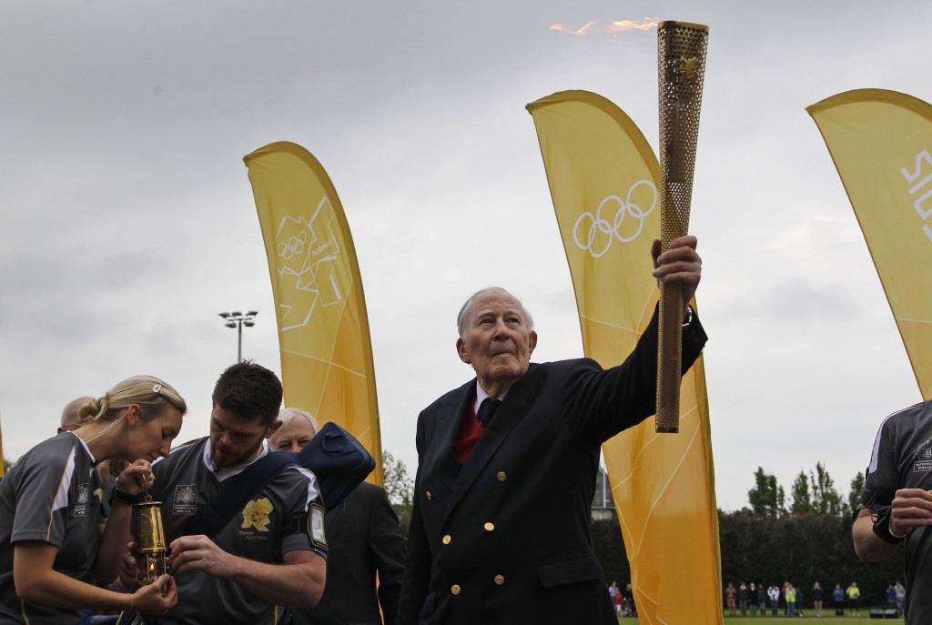 FILE - In this July 10, 2012, file photo, Sir Roger Bannister holds the Olympic Flame on the running track at Iffley Road Stadium in Oxford, England. ...